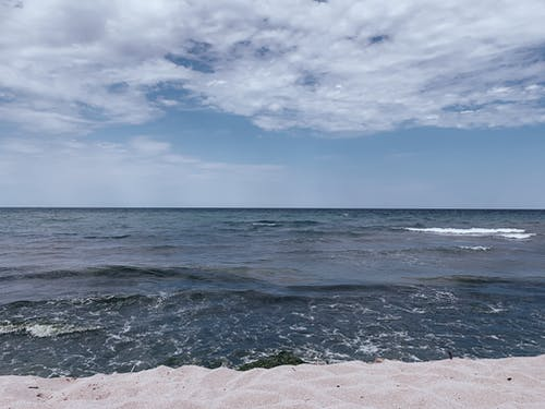Picturesque view of blue foamy sea with rippled waves under blue cloudy sky in daylight