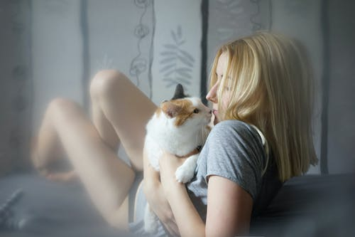 Young model and cat on bed