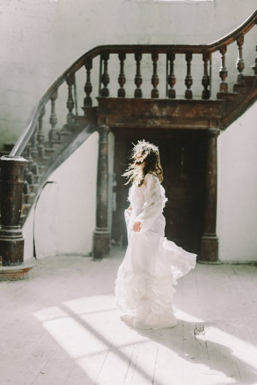 Женщина в белом свадебном платье, стоя на белом бетонном полу