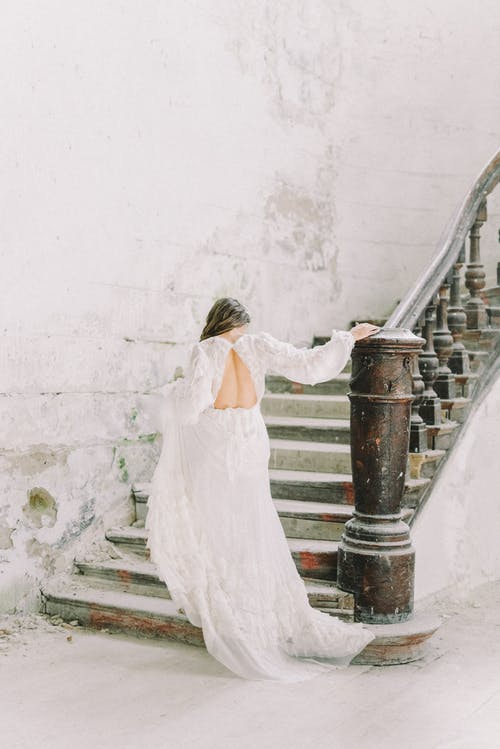 A Woman in Wedding Dress Walking Up a Staircase