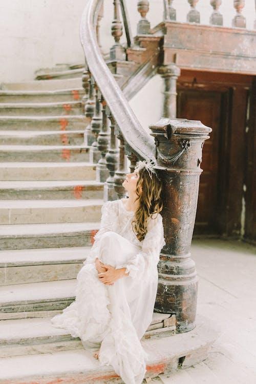 Donna In Abito Bianco In Piedi Sulla Scala Di Cemento