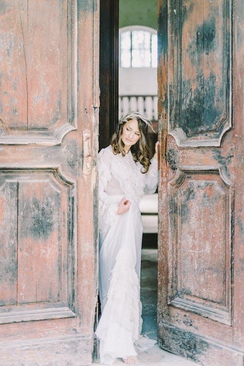 A Woman in White Dress Standing Besides a Wooden Door