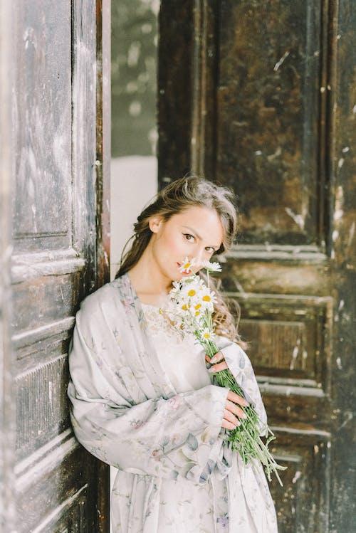 彼女の耳に白い花と白い花柄のドレスの女性