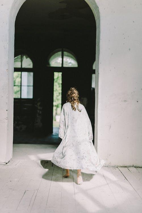 窓の前に立っている白いドレスの女性