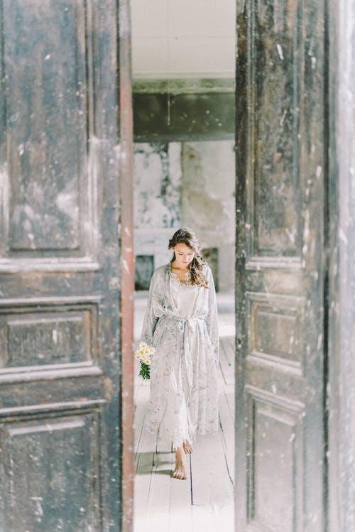 茶色の木製のドアの前に立っている白いドレスの女性