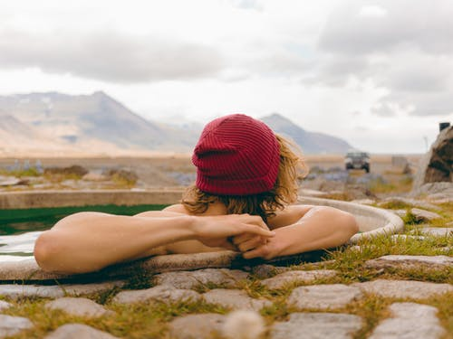 Woman in Red Knit Cap Lying on Brown Sand