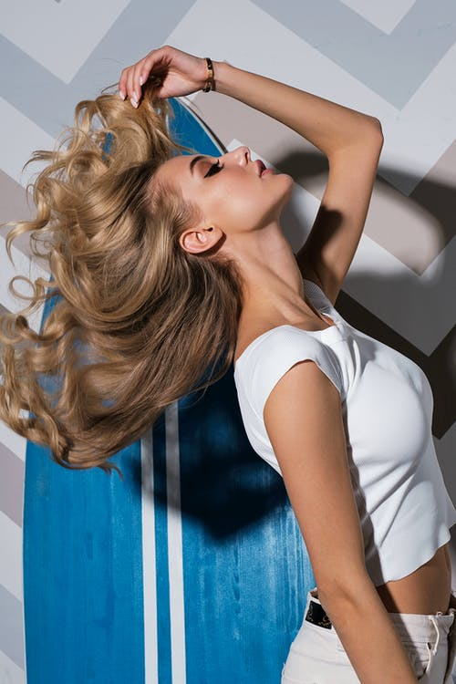 Trendy young woman standing near wall and touching hair