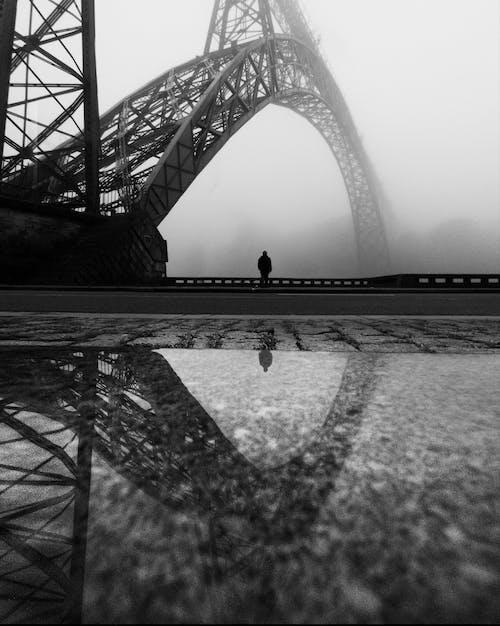 Grayscale Photo of Person Walking on Bridge