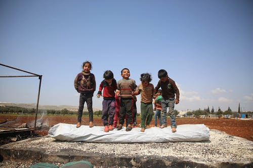 Happy children standing on destroyed place