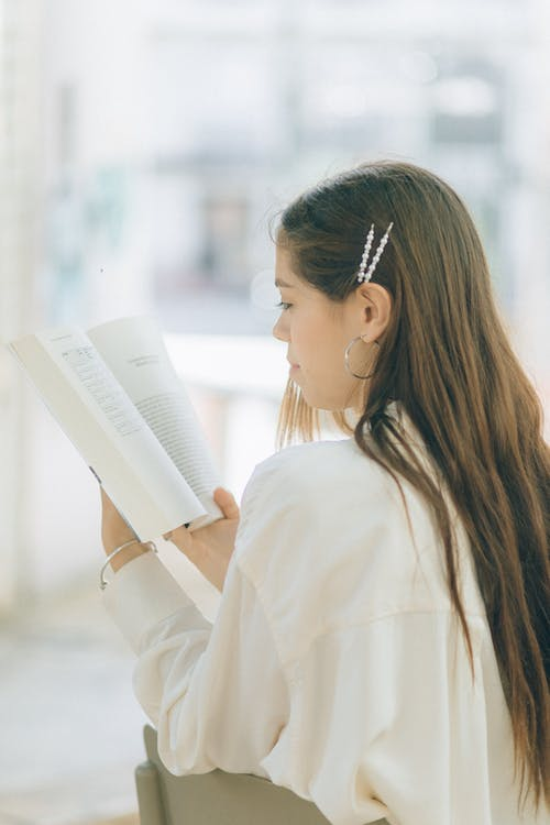 Woman in White Long Sleeve Shirt Reading Book
