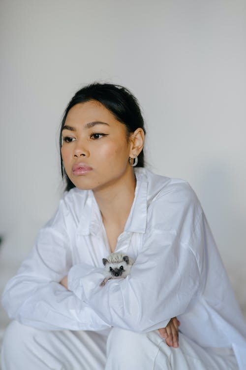 Contemplative attractive Asian female wearing stylish white clothes sitting with arms on knees in light studio and looking away pensively