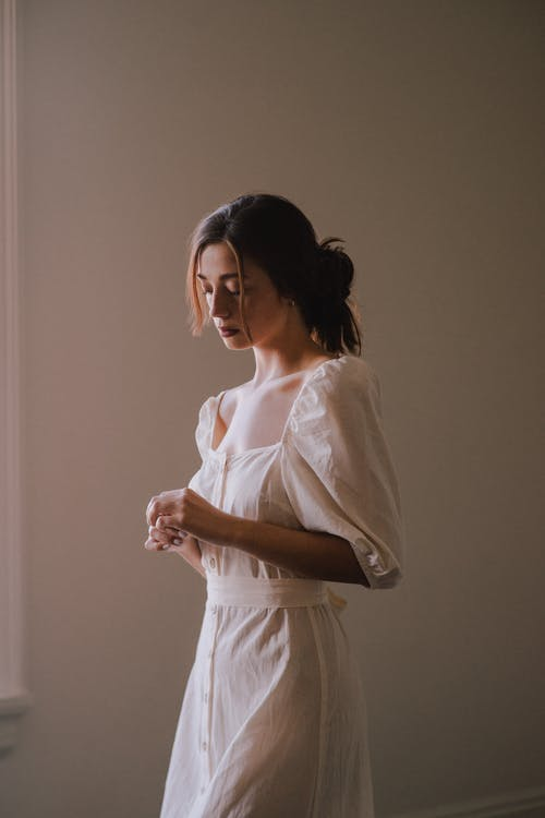 Dreamy young woman in white dress in light room