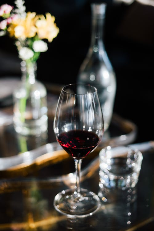 Glass of red wine on creative glass table