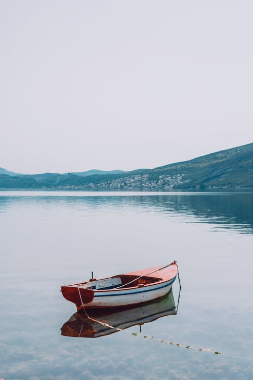 Scenery of small wooden boat moored on tranquil still pond surrounded by rough grassy hills under gray sky