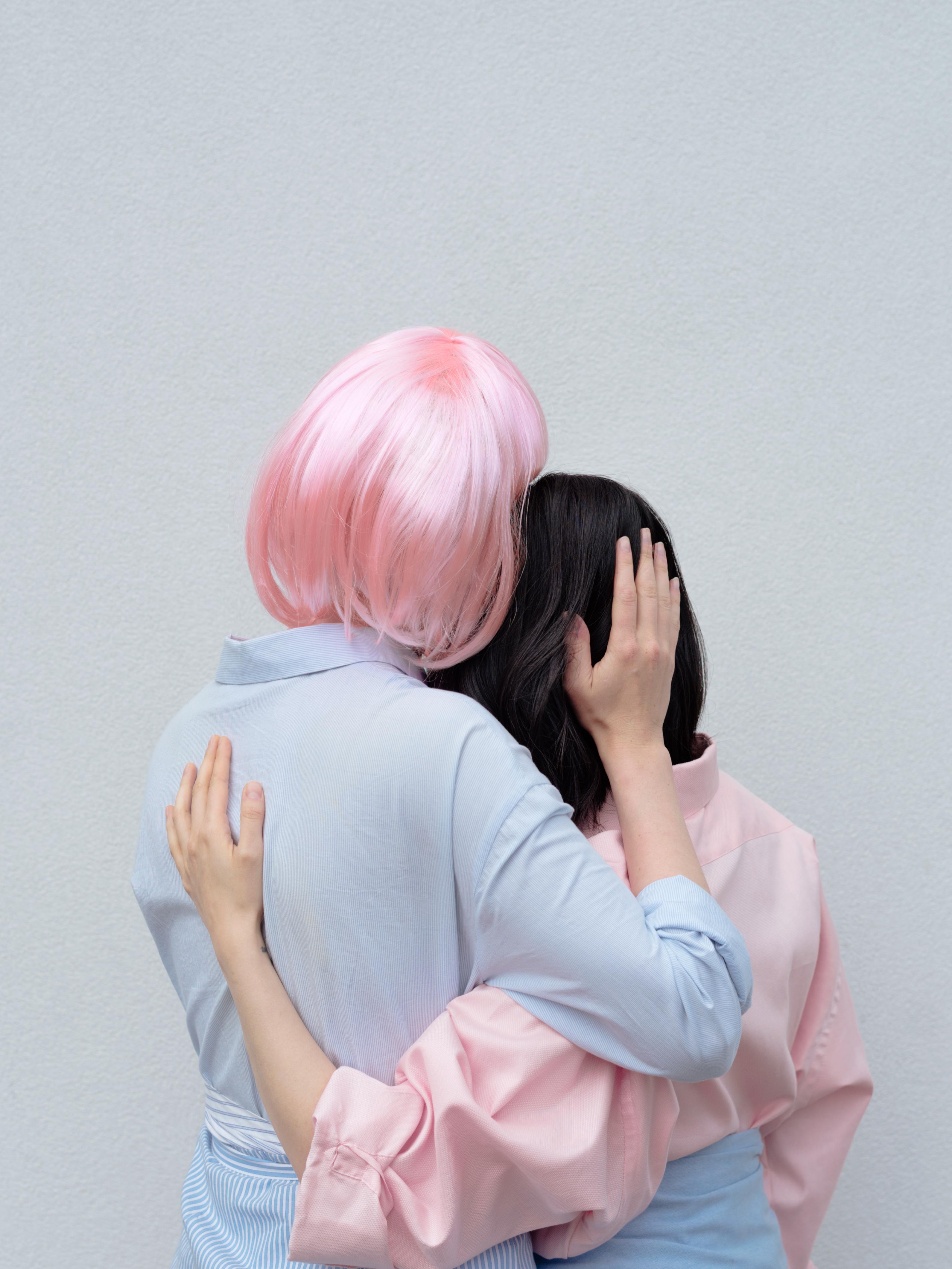 faceless women embracing gently in studio