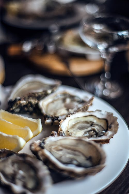 Plate with fresh delicious oysters with lemon slices served on table in fine dining restaurant