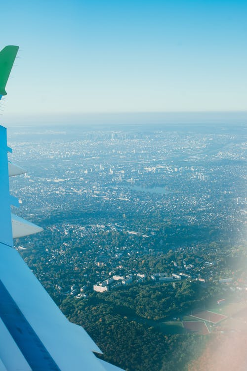 View of city with green vegetation and blue sky with horizon line from above through window of airplane flying in air