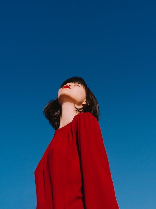 Stylish Asian woman with bright red lips enjoying sunny weather