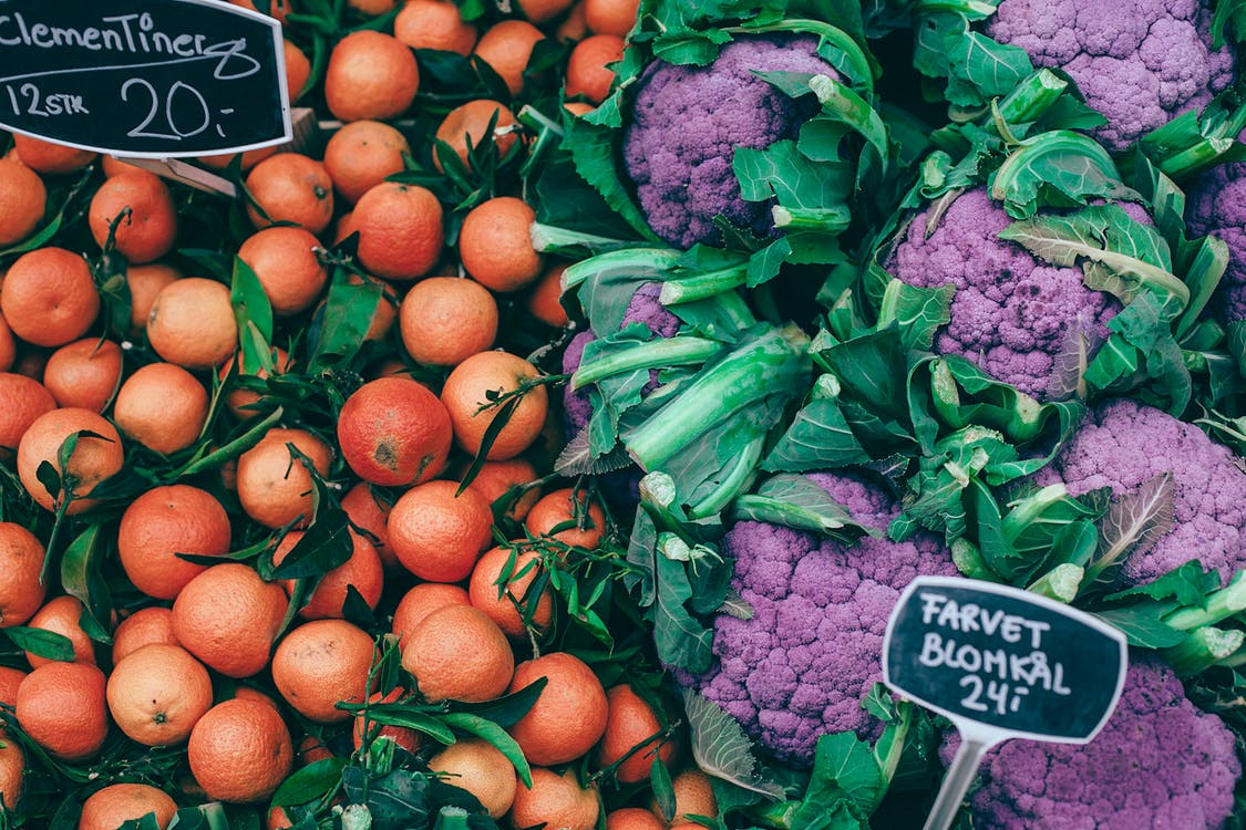 From above of fresh ripe colorful citrus fruits placed near violet healthy cauliflower on market