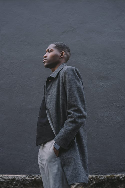 Side view of serious young African American male in formal clothes with hands in pockets standing near dark gray wall
