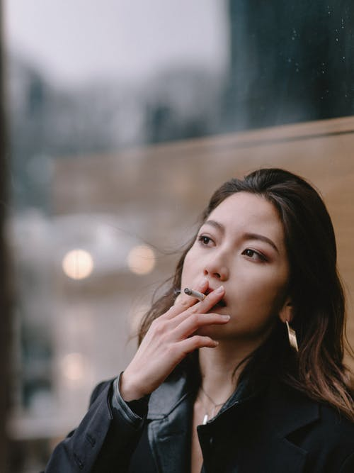 Thoughtful young woman smoking cigarette