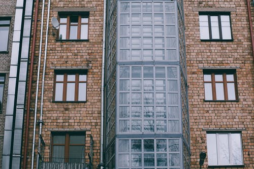 Low angle of facade of brick apartment building with windows and glass corner