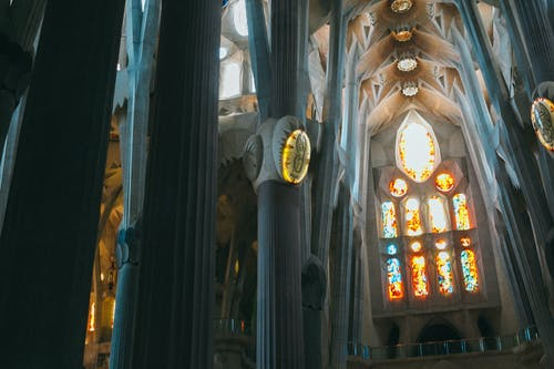From below of tall columns and ceiling in Gothic style in Catholic landmark of Spain Sagrada Familia