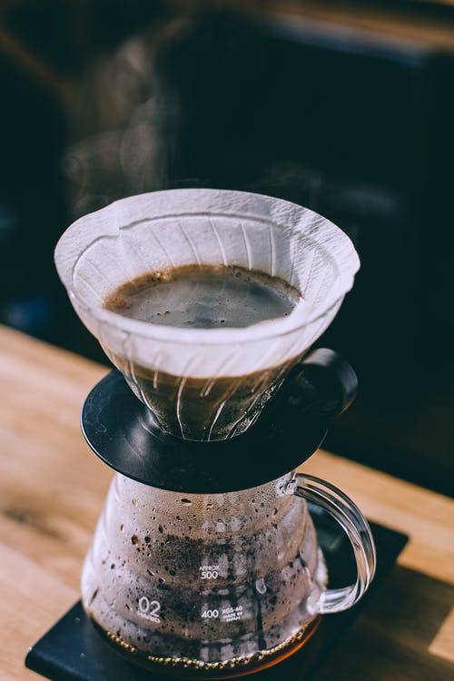 Coffee pouring into glass pot in cafe