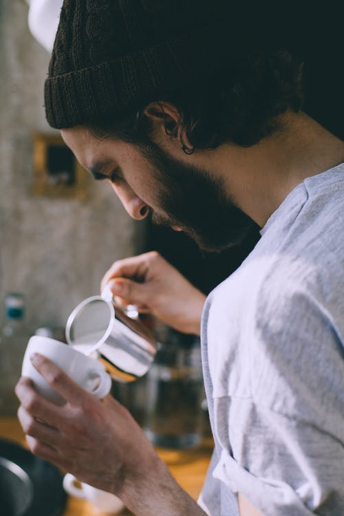 Faceless man pouring milk in coffee in cafe