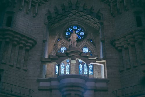 From below of Sagrada Familia basilica in Barcelona with stained glass windows and sculpture near uneven walls