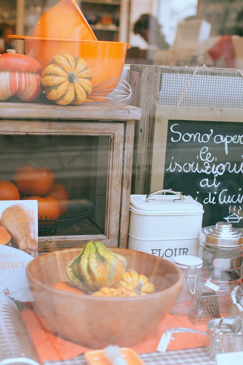 Through glass view of store front of utensils shop decorated with vegetables and small blackboard