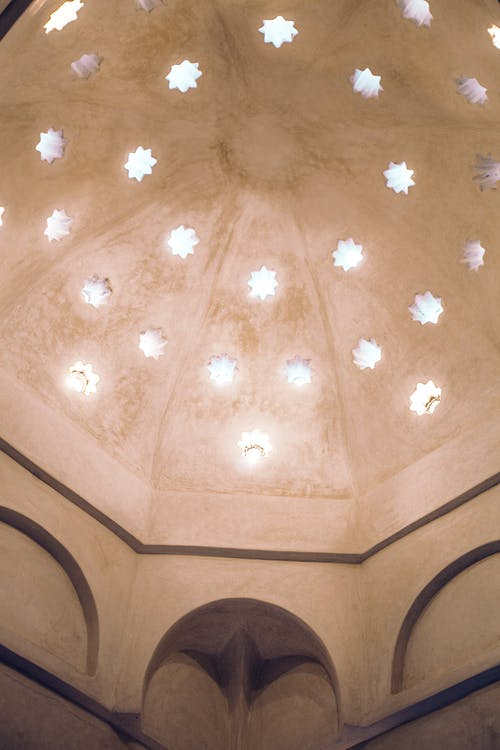 From below of arched ornamental ceiling decorated with carved stars in stone building of hammam