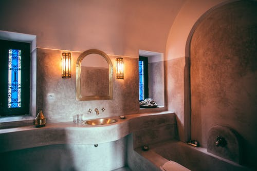 Interior design of modern spacious bathroom in Moroccan style with sink and bath made of stone