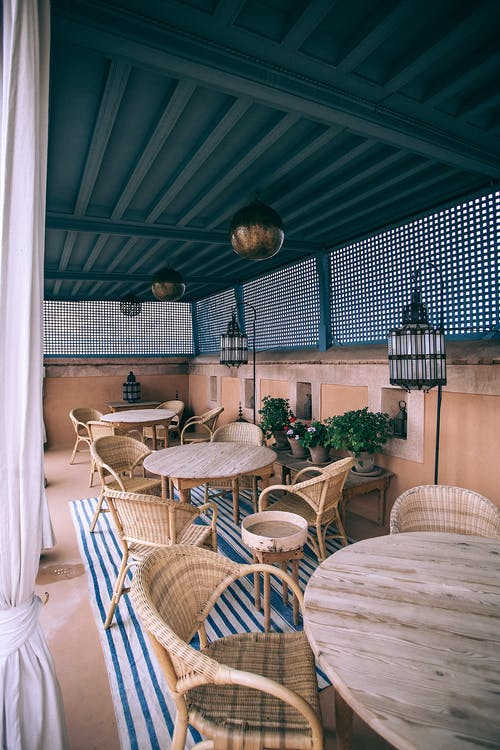 Interior design of summer terrace of cozy cafe with wooden round tables and wicker chairs