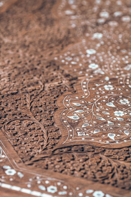 From above closeup of brown wooden table surface with carved ornamental elements and decorative details