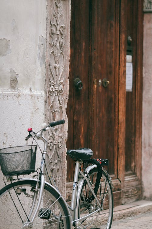 Bike with metal basket parked near shabby wall and entrance with old wooden door of residential house