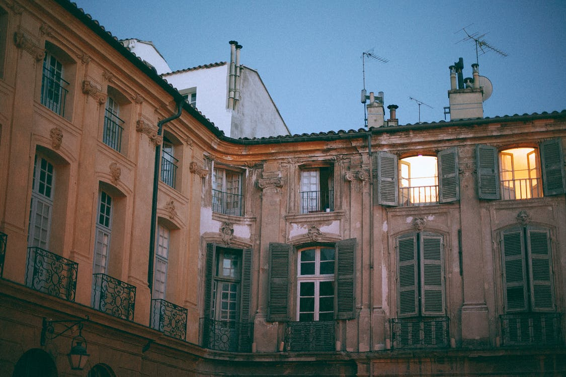 From below of facade of famous palace with pillars and shutters on windows and weathered wall located in Aix en Provence France