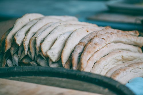 High angle of fresh delicious baked traditional Georgian shoti bread in heap in bakery