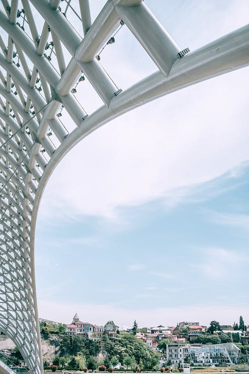 From below of famous steel framework covered with glass of modern Peace bridge located in Tbilisi Georgia on partly cloudy day
