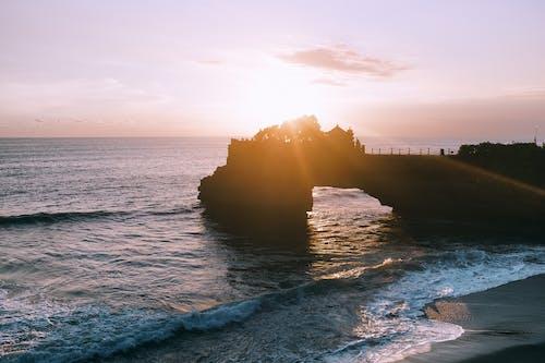 Schattenbild Der Leute, Die Auf Felsformation Nahe Meer Stehen