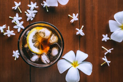 Top view of glass with fresh drink with slice of lemon and ice cubes on wooden background with plumeria flowers