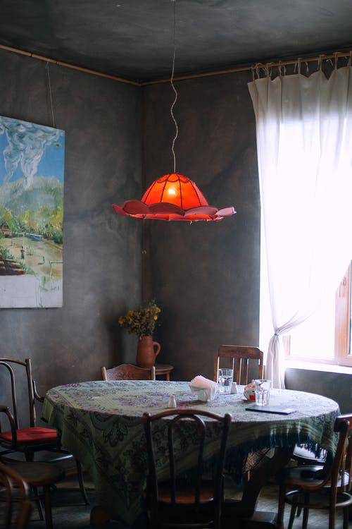 Old fashioned room interior with round table hanging red lampshade picture on wall and vase with dry flowers in corner