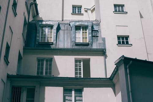 Low angle of old fashioned gray residential house with square windows at daytime