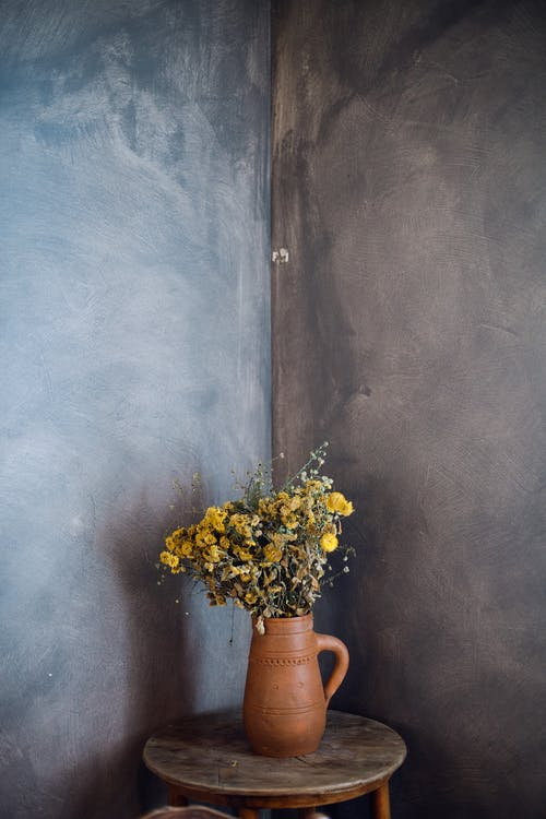 Wild flowers in pitcher in dark room