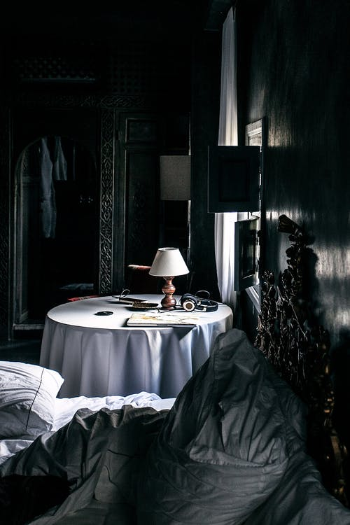 Dark bedroom in oriental style with disheveled bed with ornamental bedhead and round table near window