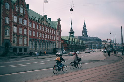 Cyclists riding along famous embankment in Copenhagen with historic Christiansborg palace and stock exchange building in Denmark on cloudy day