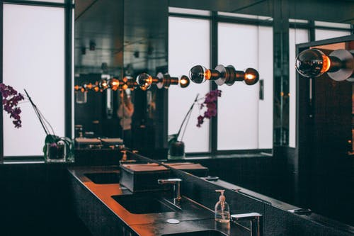 Black sinks with stainless steel faucets placed under wide mirror decorated with illuminated dark lamps in modern toilet room