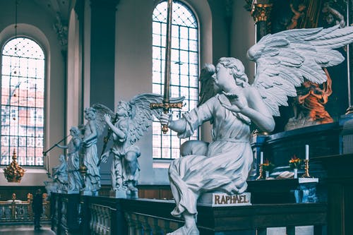 Baroque altarpiece decorated with white angels sculptures on marble railing located in Church of Our Saviour Copenhagen Denmark