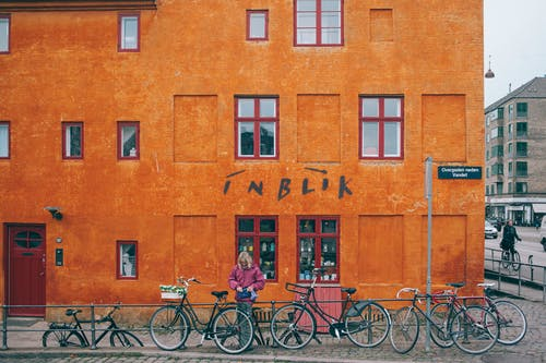 Woman parking bicycle near metal railing against colorful orange stone house with shop downstairs located in Copenhagen Denmark on cloudy day
