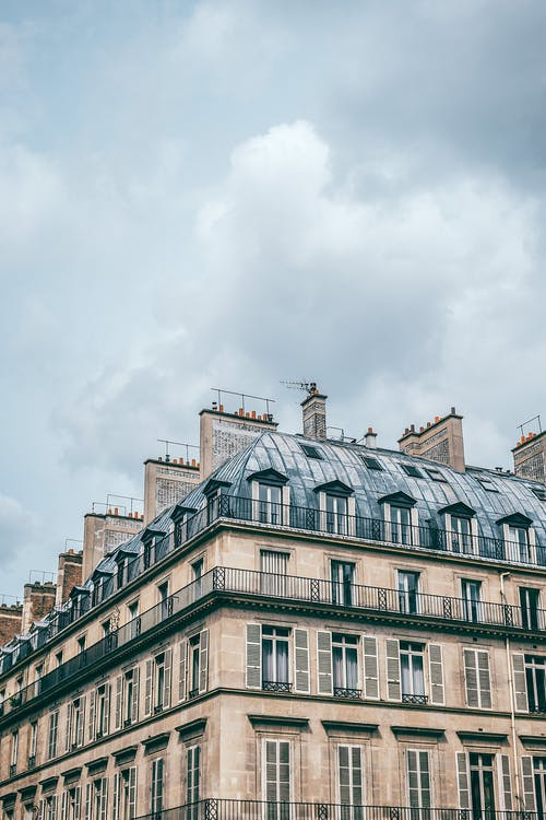 From below exterior of aged residential multistory building with slatted balconies and heating chimneys located in Paris France on cloudy day